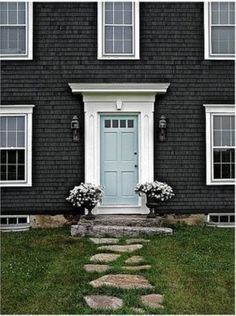 love the blue door here with the white trim against the dark house...