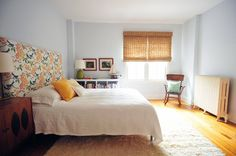 jute blinds, white rug and coverlet, floral headboard