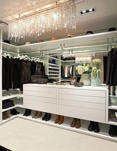 In this closet, white lacquered cabinetry and mirrored back panels combine with custom lighted hanging rods for an innovative storage design. Cantilevered black velvet bench provides seating, while a striking, rectangular crystal chandelier illuminates.