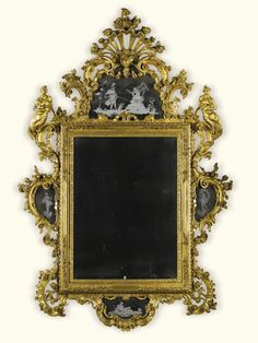 An Italian carved giltwood mirror, Venetian, mid 18th century with a rectangular bevelled plate within a leaf and scroll carved frame surmounted by an etched mirror cresting ornamented with classical figures carved with a stylised shell, flowers, mask and scrolls flanked by nereids, the apron and sides ornamented with conforming mirror plates, similarly ornamented with classical figures - Dim: 254cm high, 164cm wide; 8ft. 4in., 5ft. 4½in.
