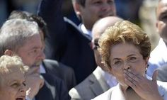 Dilma Rousseff gestures to her supporters accompanied by the former President Luiz Inacio Lula da Silva, outside the Planalto presidential palace in Brasilia on Thursday.