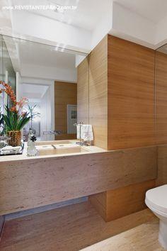 No lavabo, a mesma composição dos acabamentos de todo o apartamento: mármore e madeira lavada