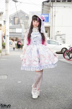 RinRin Doll is a well-known Tokyo-based model and Youtuber. She is wearing a lolita outfit from Angelic Pretty, with a flower hat, floral dress, over the knee socks and bow shoes.