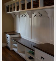 Like the shelf brackets.  Bead board divided with 2x4's.  Crown moulding.  Stained seat?