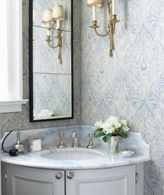 Corner vanity with blue grey woodwork paired with mirror on one wall and sconce on the other.  Elegant space