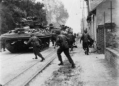 Sherman DD tanks of 'B' Squadron, 13th/18th Royal Hussars support commandos of No. 4 Commando, 1st Special Service Brigade, on the Rue de Riva-Bella as they advance into Ouistreham, Sword area, 6 June 1944.