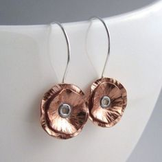 A contemporary twist on the delicate poppy flower creates these stunning eye-catching earrings. Hand-cut in an alluring contrast of recycled copper and sterling silver.Using modern design influences, the earrings have been textured, domed and. Metal Clay Jewelry, Brass Jewelry, Geek Jewelry, Gothic Jewelry, Jewlery, Jewelry Necklaces, Earrings Handmade, Handmade Jewelry, Copper Earrings