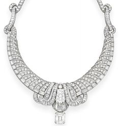 A DIAMOND NECKLACE   Suspending a cut-cornered rectangular-cut diamond, weighing approximately 8.65 carats, from a circular and baguette-cut diamond scrolling plaque, to the openwork circular-cut diamond spiral band, with a baguette-cut diamond trim and terminals, to the circular-cut diamond backchain, mounted in platinum, 13¾ ins.