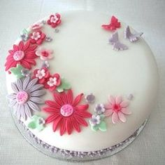 A cake covered in white icing and decorated with pink and lilac flowers