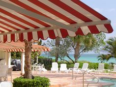 Several high quality retractable lateral folding arm awnings installed on a home in famous Golden Beach, Florida, USA