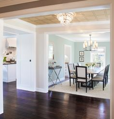 Pretty Palladian Blue look Los Angeles Transitional Dining Room Decorating ideas with area rug beige wall chandelier cool colors crown moulding dark wood floors dining chairs