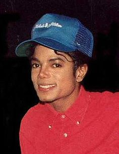 A man in a red shirt smiling toward the camera. Atop his head is a blue baseball cap. ~ M J