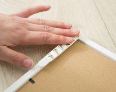 Posez les languettes tableaux adhésives sur votre cadre et fixez le au mur en ajustant bien la pose avec votre niveau.