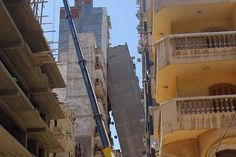 A high-rise residential building leans against another building after toppling over in a central neighborhood of Alexandria, Egypt,June 1, 2017.