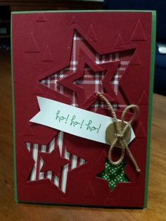 handmade Christmas card ... trio of die cut negative space stars with plaid and striped paper backings ... mostly burgundy with bits of white, green and kraft ... luv the starts an the popped star centers ...