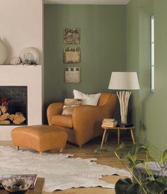 olivgrüne Wandfarbe und Ledersessel mit Hocker