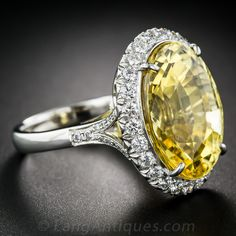 29.13cts. Natural Yellow Ceylon Sapphire Ring. Perfect in every way! This 29 carat yellow sapphire has it all, a clear bright yellow color, a perfect cut to reflect and refract light from all the facets, in a beautifully proportioned eye pleasing oval. And it is certified by the AGL laboratory to be natural in color with no heat or clarity enhancement. A real GEM. Circled by a delicate border of sparkling diamonds and set in a basket weave gallery this stone is ready to grace your hand.