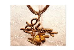 Liberace vintage costume necklace pendant has his name in script & piano with candelabra 3 chain necklace  https://www.etsy.com/listing/173296431/liberace-vintage-costume-necklace?