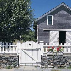 Stone wall topped with white-picket fencing both screens and welcomes visitors. | Photo: Walpole Woodworkers. | thisoldhouse.com