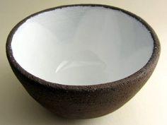 """Ce bol en céramique a été façonné à la main pour la marque Najel de la SAS NAJJAR / FRANCE. Fabriqué en série limitée en terre brune foncée et émaillé à l'intérieur avec un émail blanc brillant, chaque bol porte la signature """"SL"""" de la créatrice Saskia Lauth."""
