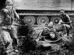 During an ambush by Viet Cong guerrillas, an officer shouts orders as a wounded American soldier awaits evacuation near Saigon during the Vietnam War, 1969. The soldier is attended by a medic as they seek cover beside an armored troop carrier.