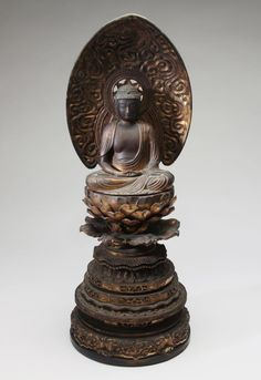 Japan; Edo Period, c. 18th century Seated on lotus pad, a deeply carved mandorla behind. The base is particularly well carved and very intricate. Very high quality