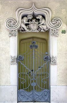 Barcelona, detailed carving of dog and monkey over a crest above the door. Rose crested wrought iron gates.