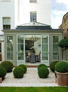 Conservatory with topiary box balls. Try Little Greene Normandy Grey for a similar soft, chalky grey green paint. Details on Relics Of Witney blog