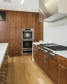 The modern kitchen in this home makes use of natural beauty with these zebra wood cabinets. The grain of this exotic wood gives the  cabinets an ornamental quality without being overbearing-perfect for the no-nonsense feel of a modern design. The white countertops accent the grain of the wood, making it the showpiece of the space.