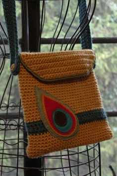 I could add a felt peacock feather (in realistic colors) on a crocheted bag!