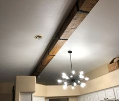 Beautiful reclaimed rough sawn boards wrap around an existing ceiling support beam to create the look of a solid wood beam. Out Of State Move, King Size Bed Frame, Barn Wood Projects, Wood Beams, Wood Pieces, Ceiling Fan, Floating Shelves, Solid Wood, Cool Designs