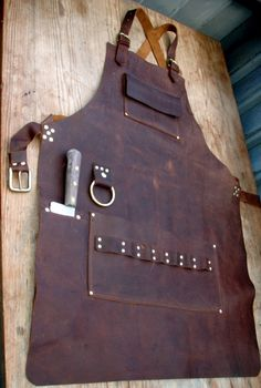 I made this leather apron as a custom order for a guy who wanted it all in his kitchen. The knife pocket holds a large chefs knife and the brass