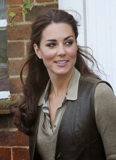 Kate wearing a Burberry military-pocket blouse, a taupe v-neck sweater, and a leather vest from Really Wild
