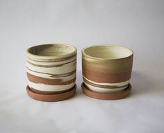 Wheelthrown planter made from smooth porcelain marbled with sandy red clay. The inside is glazed and outside is raw clay. There is a hole in the bottom, and the