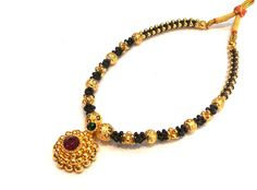 A traditional Maharashtrian thushi necklace is based on the traditional styles of Kolhapur, in southwest Maharashtra. The necklace is known for its lightweight feel, which is useful considering the bride is wearing quite a lot of gold jewelry on her wedding day. A Kolhapur thushi will always have a dora (string) to tie the golden balls of the necklace together.