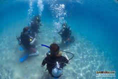 Instructor Kerry demonstrates a few skills for his students to master during the buoyancy check confined water dive..