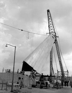 """1956. """"De Boeg"""" een drijvende bok zet het belangrijkste gedeelte van het Nationaal monument voor de Koopvaardij op de betonnen sokkel."""
