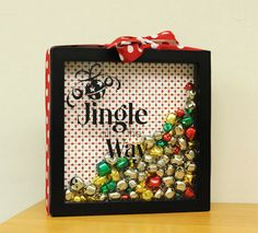"""Shadowbox Frame """"Jingle All the Way"""" Vinyl Bells Supplies  Patterned Scrapbooking Paper Mod Podge Ribbon Scissors  1.  Wipe down the glass of the shadowbox frame. 2.  Apply the vinyl to the outside of the glass. 3.  Open the frame and use the scissors to cut the paper to fit the back of the frame. 4.  Use Mod Podge to adhere the paper to the back of the frame. 5.  Fill the shadowbox with various bells."""