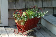 What a great idea.  If you come across an old  magazine rack during your travels (or if you already have an old one) why not transform it into a beautiful garden planter for the deck or porch.  Wouldn't this look amazing by the front door.  So welcoming!