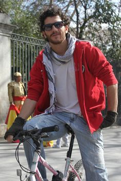 Parece que con el fin de febrero la primavera se asoma a Madrid y con ella vuelven a proliferar los ciclistas que parecen haber encerrado bajo llave  los abrigos y bufandas, así como los colores y tejidos pesados.    Nuestro chico de hoy le rinde homenaje a los básicos: jeans, camiseta blanca y sudadera roja con capucha le confieren una imagen perfecta para este paseo. Los complementos: pañuelo palestino, wayfarer, mitones y cómo no, su bici,  terminan y definen el look.