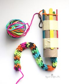 "I've been busy working on setting up a project for my sons 1st grade class! It's an easy ""knitting"" project that is perfect for elementary age kids. With a cardboard roll, tape, and popsicle sticks, y"