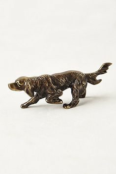 Successful tablescapes require objects of varying sizes, heights, and materials to offer a dynamic mix.  Bronze dog doubles as a bottle opener! Anthropologie.com