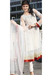 White net readymade Anarkali kameez is designed with thread, stone, sequins, cutbeads, applique and patch border work. As shown matching shantoon churidar, net dupatta and sleeve is available. Shimmer fabric is used as lining of the kameez. Available kameez and sleeve length is 43 and 21 inches.(Slight variation in color is possible.)