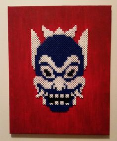 The Blue Spirit Mask from Avatar: The Last Airbender. Made with Perler on a red canvas