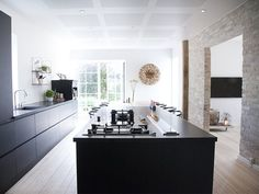 love the juxtaposition of the sleek black kitchen against the exposed brick walls.