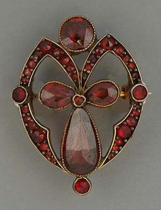A bohemian garnet brooch, circa 1910, set to the centre with three pear-shaped garnets, to an openwork border set with rose-cut garnets.