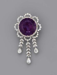 A BELLE EPOQUE AMETHYST AND DIAMOND BROOCH   The circular-cut amethyst within the diamond garland surround, suspending a graduated fringe of diamond leaves to the three pear-shaped drops, millegrain setting, mounted in platinum and gold, circa 1900, 6.9 cm. high