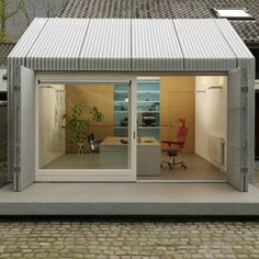A home office in Eindhoven created by wrapping a garage in corrugated aluminium.