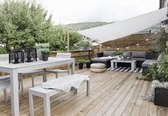 Una terraza para soñar! Terrace, grey textiles, string lights, puff, concrete table, wooden floor, plants.