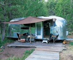 """Guesthouse  A pair of 1960s-style butterfly chairs flank the entrance to the 1960s silver Airstream trailer the couple offer to their guests. """"The interiors are redesigned in an Army-surplus style,"""" the designer says. A canopy over the wood-plank platform protects visitors from the elements."""